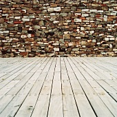 Wooden floor in front of stone wall