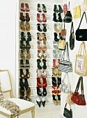 Ein gefülltes Schuhregal und eine Handtaschensammlung, daneben ein antiker Stuhl