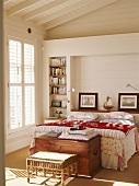 Ein Bett im Mustermix mit antiker Truhe am Fußende in einem hellen Schlafzimmer mit Holzverkleidung