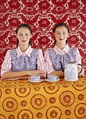 Twins sitting at table in front of bright wallpaper