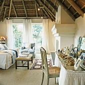 Die traditionelle Holzdecke bildet einen starken Kontrast zur eleganten Wohnzimmereinrichtung mit romantischem Schminktisch