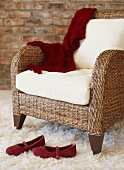 Rattan armchair and red ladies' shoes on flokati rug