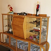 CDs & various ornaments in glass-fronted cabinet