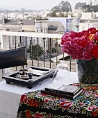 Flowers, books & breakfast tray on balcony table