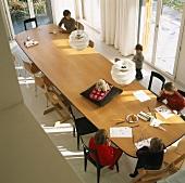 Aufsicht auf einem großen Esstisch mit malenden Kindern