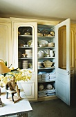 A cupboard with crockery and table linen