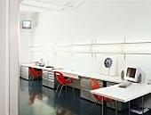 weiße Arbeitstische und rote Schalenstühle in einem Büro