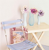 Ein Holzklapptisch mit Blumen und ein violetter Klappstuhl