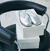 Silberne Hausschuhe und weiße Schuhkartons auf schwarzen Lederstuhl