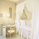 Weißes Himmelbett und verspiegelter Tisch mit Glasvasen im hellen Schlafraum