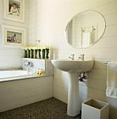 Badezimmer mit freistehendem Waschbecken und rundem Wandspiegel neben Badewanne