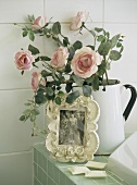Picture and roses in jug on edge of bathtub