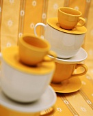 Yellow and white cups and saucers