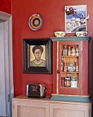Small cabinet of spices, toaster & African painting in kitchen