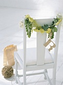 Garland of plants on chair backrest