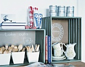 Wooden cutlery in wooden crates on kitchen worksurface