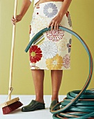 Woman holding hose and broom