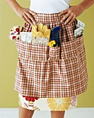 Woman with gardening tools in apron pockets