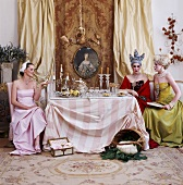 Three women in Baroque clothing sitting around dining table