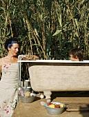 Mother bathing son in garden bathtub