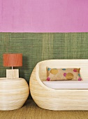 Wooden couch and table lamp against two-tone wall