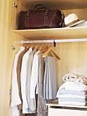 Clothing and bed linen in wardrobe