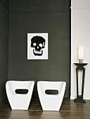 Zwei weisse Stühle vor dunkler Wand