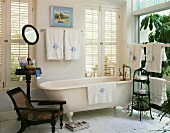 Bright bathroom with free-standing bathtub and antique furniture