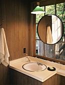 Washstand with basin below round mirror hung on lattice window