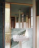 Pedestal sink below large mirror on marble-clad wall