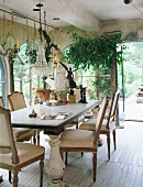 Dining table and antique, shabby-chic chairs in traditional conservatory