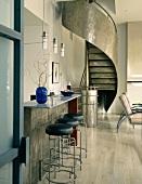 Modern, metal spiral staircase behind breakfast bar in open-plan interior