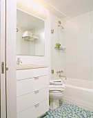 Bright, white bathroom with toilet and mosaic tiles on floor