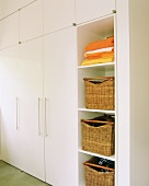 White fitted cupboards and open-fronted shelves of storage baskets