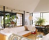 Wohnzimmer mit großer, weisser Eckcouch; dahinter eine überdachte Terrasse mit einem Korbstuhl und eine exotische Zimmerpflanze