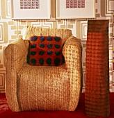 Aussergewöhnlicher Korbsessel mit Filzkissen und orangefarbener Stehlampe daneben; dahinter eine Wandtapete im Stil der 70iger Jahre