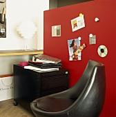 Arbeitsecke mit schwarzem Rollcontainer vor einer roten Pinwand; davor ein schwarzer Designersessel
