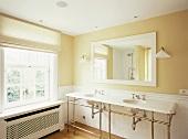 Blick auf einen Waschtisch mit Metallfüssen, einem rechteckigen, gerahmten Badezimmerspiegel in einem traditionellen Badezimmer