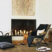 Modernes Wohnzimmer mit Kerzendeko im offenen Kamin und einem ausgefallenen Liegestuhl mit Pelzbezug