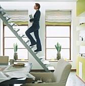 Frau geht eine Treppe in Wohnraum ohne Geländer hoch