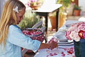 A little girl sprinkling rose petals on a laid table