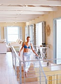 Woman wearing beachwear walking down stairs in house