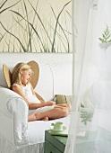 Girl wearing cardboard wings sitting on white sofa
