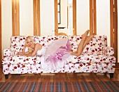 Frau mit festlichem Kleid liegt auf geblümtem Sofa