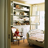 Little girl sitting on chair in front of cupboard in child's bedroom