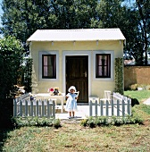 Little girl in front of shed with picket fence