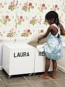 Kleines Mädchen räumt Spielsachen in eine Box