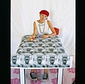 Girl drinking cup of coffee sitting at table with photo-print tablecloth with African motif