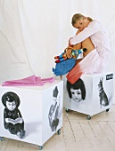 Girl sitting on toy box on castors