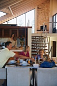 Family eating meal in open-plan interior with kitchen and mezzanine